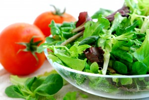 Fresh baby greens salad and tomatoes close up